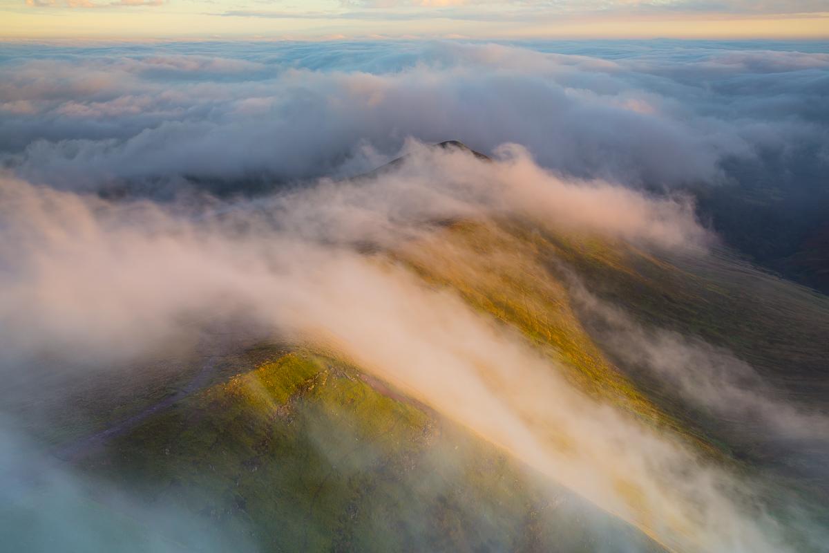 Clouds roll over the Cefn Cwm Llwch ridge at sunrise.